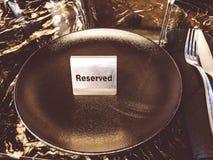 Reserverad tabell, logo Boka emblemet, tabell i restaurangen hungrigt upptaget Royaltyfri Bild