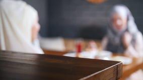 Reserverat tecken på tabellen Muslim kvinna som två sitter på bakgrunden och samtalet En person tar bort tecknet från stock video
