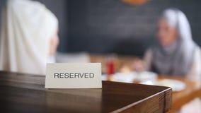 Reserverat tecken på tabellen Muslim kvinna som två sitter på bakgrunden och samtalet stock video