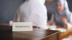 Reserverat tecken på tabellen Två muslim kvinnor sitter ner tabellen på bakgrunden lager videofilmer