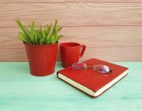 Reservieren Sie Glastopf mit roter Tasse Kaffee-Weinlese des Grases auf hölzernem Konzept der Tabelle Lizenzfreie Stockfotos