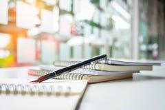 Reservieren Sie und Stift auf Tabelle mit Sonnenlicht, kopieren Raum Stockbild
