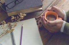Reserviert gelbe Kaffeetasse des Griffs auf einem Holztisch mit trockenem Blumennotizbuch der Gläser und Bleistift - Tonweinlese Lizenzfreie Stockfotos