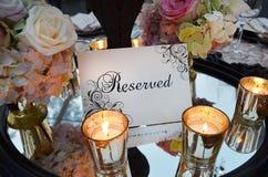 Reservierungszeichen mit Hochzeitsblumenstrauß und Gläser auf Tabelle lizenzfreies stockbild