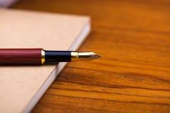 Reservoarpenna eller bläckpenna med anteckningsbokpapper på träarbete ta Royaltyfria Bilder
