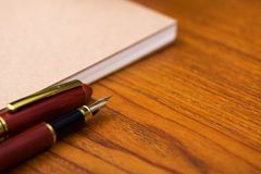 Reservoarpenna eller bläckpenna med anteckningsbokpapper på träarbete ta Royaltyfria Foton