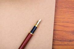 Reservoarpenna eller bläckpenna med anteckningsbokpapper på träarbete ta Arkivfoto
