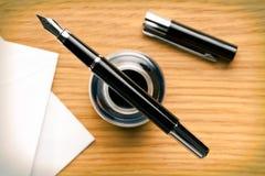 Reservoarpenna och bläckhorn på skrivbordet royaltyfria foton