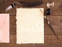 Reservoarpenna och tomt papper på den lantliga wood tabellen för turkos Arkivfoton