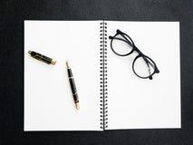 Reservoarpennan med anteckningsboken på svart texturerade bakgrund för häftebegrepp Arkivfoton