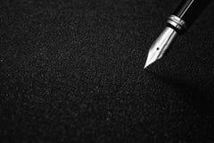 Reservoarpennan med den snabba banan på svart texturerade bakgrund för häftebegrepp Royaltyfri Foto