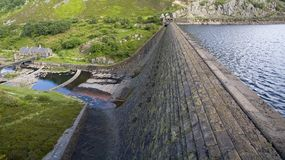 Reservoir and dam with high water level overlooking pumping station Royalty Free Stock Image