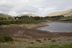 Reservoir drying up. Water supply high in the Welsh mountains shows dropping water levels. Good image to illustrate UK's impending water crisis this Summer royalty free stock photography
