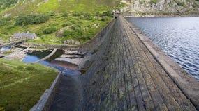 Reservoir en dam met hoogwaterniveau dat pompstation overziet royalty-vrije stock afbeelding