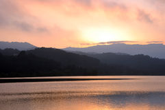 Reservoir and mountains at twilight sunset. Stock Photos