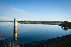 Resevoir reflections. Water tower perfectly reflected in the still waters of the reservoir Royalty Free Stock Photography