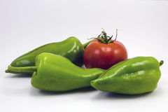 Fresh green bell peppers (capsicum) and a tomato on a white background stock photos