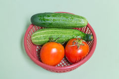 Resh tomato and cucumber in the red basket Stock Images