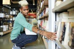 Reshelving Bücher der ernsten Buchhandlungsarbeitskraft stockfoto