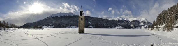 Resia ha ghiacciato il lago ed il panorama della campana della torre Fotografia Stock
