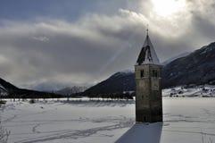 Resia ha ghiacciato il lago, la campana della torre ed il sole Fotografie Stock Libere da Diritti