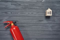 Residence fire safety. Top view of red fire extinguisher and small house on wooden planks royalty free stock photo
