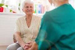 Home caregiver and senior adult woman stock photo
