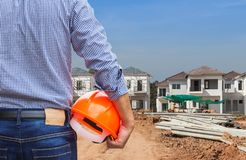 Resident engineer holding yellow safety helmet at new home building under construction site. Residential development concept Stock Photography