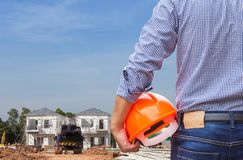 Resident engineer holding yellow safety helmet at new home building under construction site. Residential development concept Stock Images