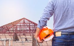 Resident engineer holding yellow safety helmet at new home building under construction site. Residential development concept Stock Photos