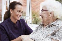 Residente fêmea que senta-se na cadeira e que fala com a equipe de tratamento no lar de idosos fotografia de stock