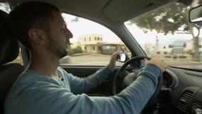 Residente masculino feliz que va sobre su negocio que da vuelta con confianza al volante almacen de video