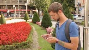 Residente urbano masculino activo que comprueba el app móvil en el smartphone, forma de vida grande de la ciudad metrajes