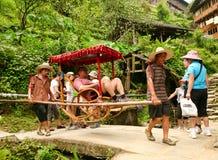 Residentes da vila de Dazhay para tomar o turista acima da montanha para reduzir em terraços do arroz fotografia de stock royalty free
