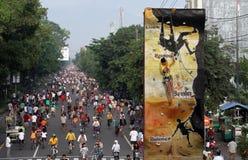 Residenti che ciclano lungo la via principale della città dell'assolo Immagine Stock