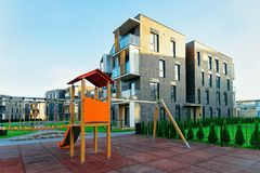 Residential apartment home building exterior children playground. Residential apartment home building exterior concept. Children playground outdoor facilities royalty free stock images