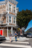 Residential architecture in San Francisco. Colorful building facades with a trees near it. Tourists walking on the streets and cro. Tourist walking on the royalty free stock photos