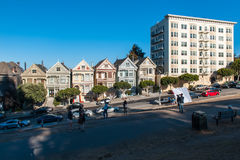 Residential architecture in San Francisco. Colorful building facades with a trees near it. Tourists walking on the streets and cro. Tourist walking on the stock photo