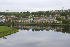 Residential area buildings reflect in Nidelva river on a cloudy day in Trondheim, Norway. Stock Photography