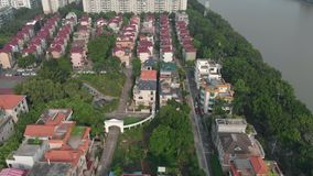 Residential area with houses, trees and park areas. In the frame we see a residential area. Between the houses there are trees, park areas. A river flows at the stock footage