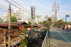 Residential area under the bridge. Common cables everywhere. Bangkok, Thailand Stock Photos