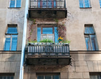 Residential balcony decorated with flowers on facade of the old Royalty Free Stock Image