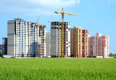 Residential building. S, some of them under construction, with beautiful green field foreground royalty free stock images
