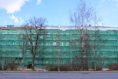 The residential building, covered with building scaffolding and green mesh, which protects passers-by from the fall of constructio. N debris Royalty Free Stock Image