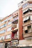 Residential building in Istanbul with balconies decorated with flowers and small Turkish flags. Turkey. Ordinary people Royalty Free Stock Photo