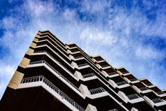 Free Residential Building Of Symmetrical Architectural Patterns With Blue Clouds Background, Real State Concept Stock Photography - 168807042
