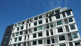 Residential building soars into blue sky. A recently-built low-rise condominium soars into blue sky Stock Photography