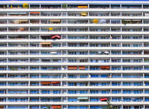 Residential building wall balconies umbrellas. Wall of tall residential building, background of balconies with colorfull umbrellas and awnings Royalty Free Stock Photography