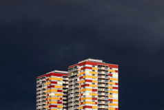 Residential buildings against stormy sky. Two colorful residential buildings against stormy dark blue sky. Abstract looking high contrast picture with copy space Royalty Free Stock Photo