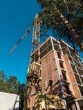 Residential buildings cunstruction place with a cunstruction crane. Royalty Free Stock Photo